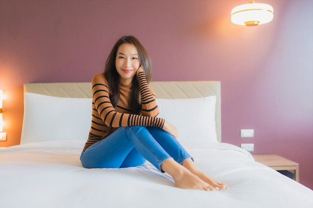 美しい若いアジア女性の肖像画笑顔ベッドでリラックス