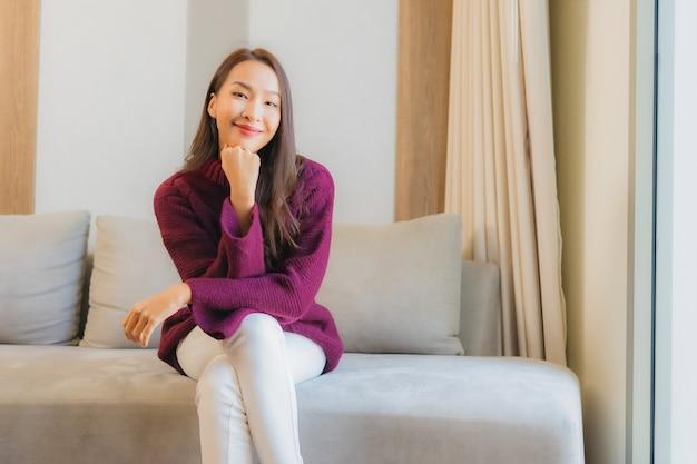 Улыбка женщины портрета красивая молодая азиатская ослабляет на софе в интерьере живущей комнаты