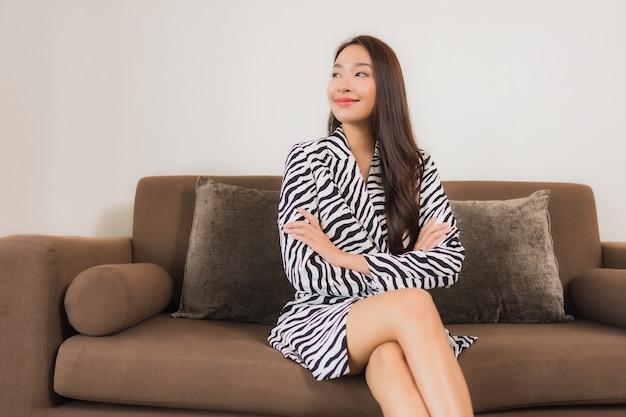 肖像画の美しい若いアジア女性の笑顔は、リビングルームのインテリアのソファーでリラックスします。