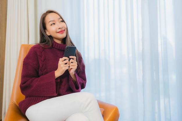 Il bello giovane sorriso asiatico della donna del ritratto si rilassa sul sofà nell'interno del salone