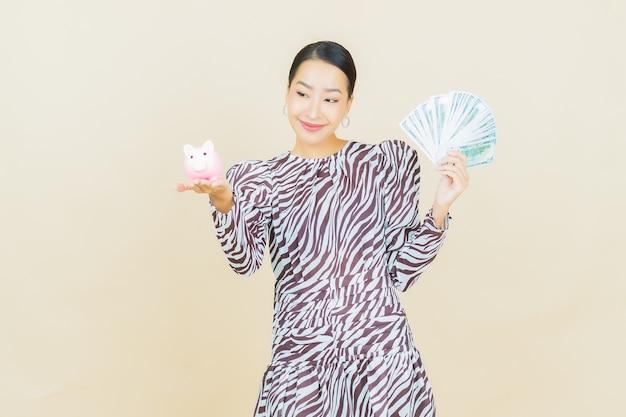 베이지 색에 현금과 돈을 많이 가진 세로 아름다운 젊은 아시아 여자 미소