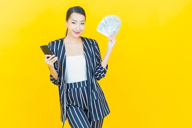 아름다운 젊은 아시아 여성의 초상화는 많은 현금과 돈을 배경으로 웃고 있다