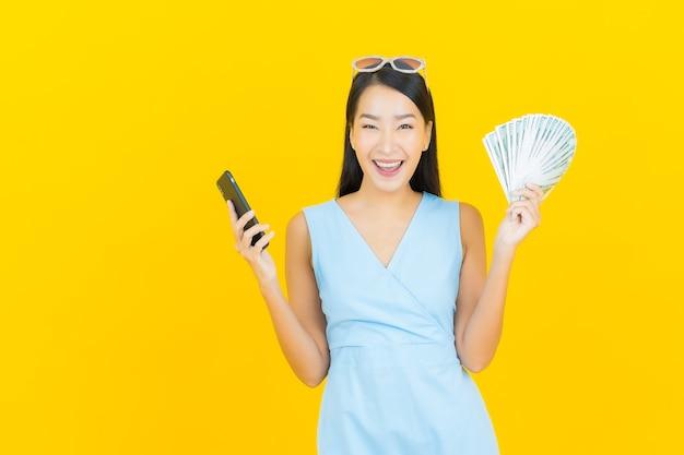 노란색 벽에 현금과 돈을 많이 가진 초상화 아름 다운 젊은 아시아 여자 미소