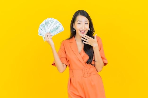 Улыбка женщины портрета красивая молодая азиатская с много наличными деньгами и деньгами на желтом