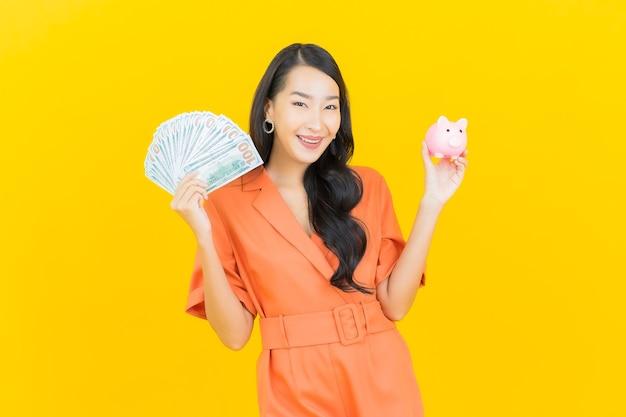 노란색에 현금과 돈을 많이 가진 초상화 아름 다운 젊은 아시아 여자 미소