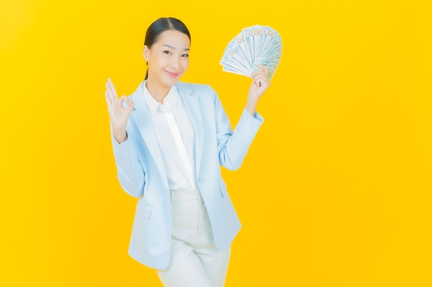 Улыбка женщины портрета красивая молодая азиатская с большим количеством наличных денег и денег на желтом
