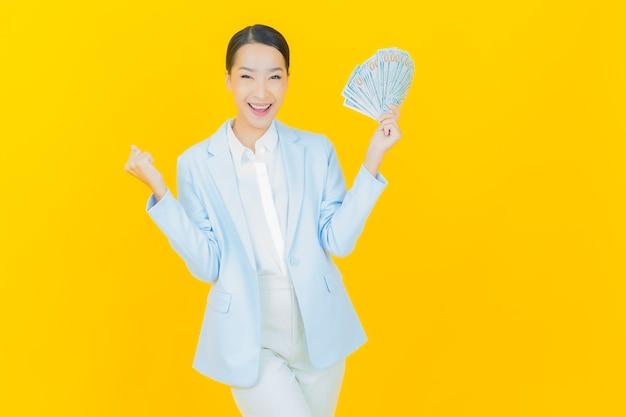 肖像画美しい若いアジアの女性は黄色にたくさんの現金とお金で笑顔