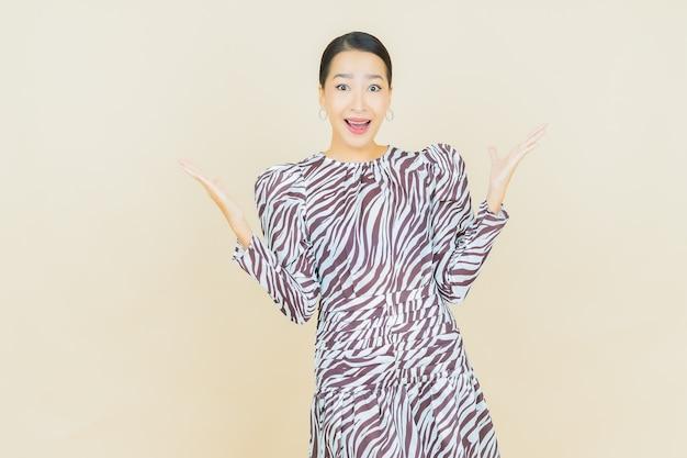 Ritratto bella giovane donna asiatica sorriso con azione su beige