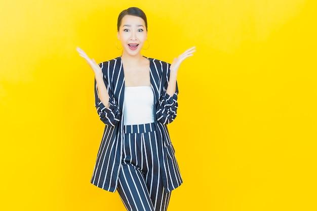 Sorriso di bella giovane donna asiatica del ritratto con azione sul fondo di colore