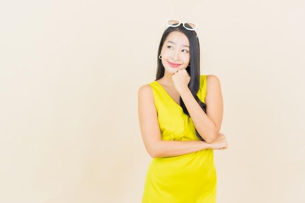 Sorriso della bella giovane donna asiatica del ritratto con azione sulla parete crema