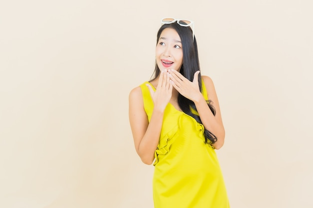 Portrait beautiful young asian woman smile with action on cream wall