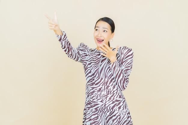ベージュのアクションで笑顔の美しい若いアジア女性の肖像画