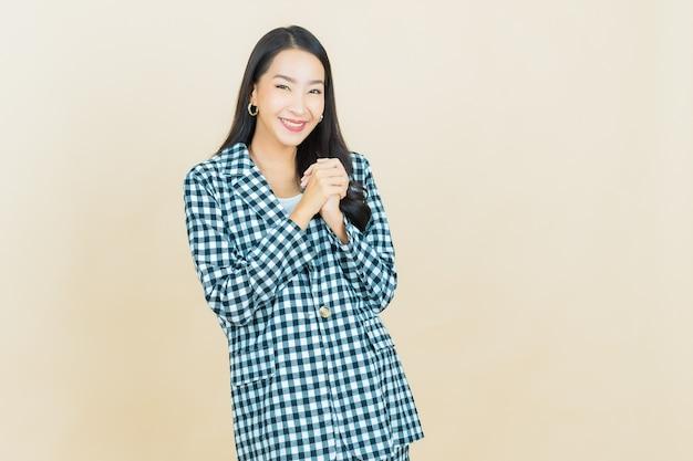 세로 아름 다운 젊은 아시아 여자 베이지 색에 대 한 조치와 미소