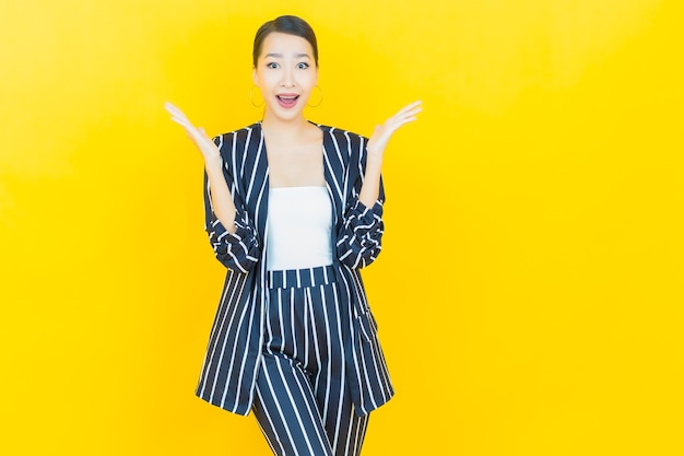 세로 아름다운 젊은 아시아 여자는 색상 배경에 행동으로 미소