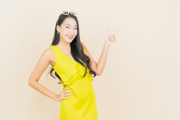 Улыбка женщины портрета красивая молодая азиатская с действием на кремовой стене