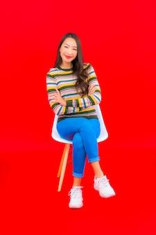 세로 아름 다운 젊은 아시아 여자 빨간색 격리 된 벽에 행동으로 미소