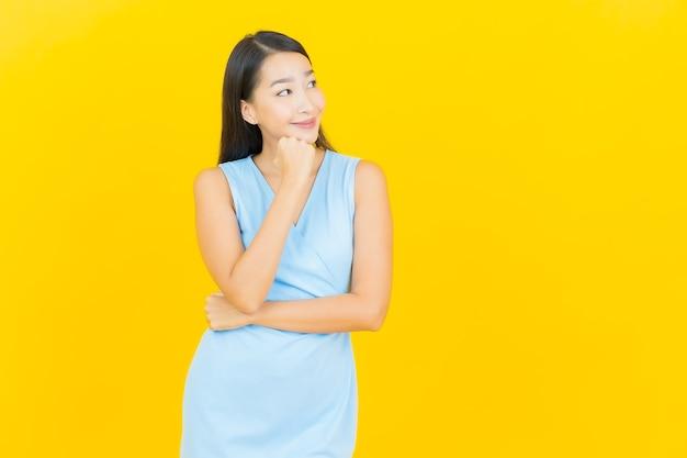 노란색 벽에 행동과 초상화 아름 다운 젊은 아시아 여자 미소