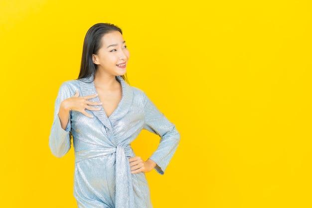 Улыбка женщины портрета красивая молодая азиатская с действием на желтой стене