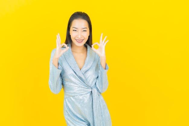 黄色の壁にアクションと肖像画美しい若いアジアの女性の笑顔