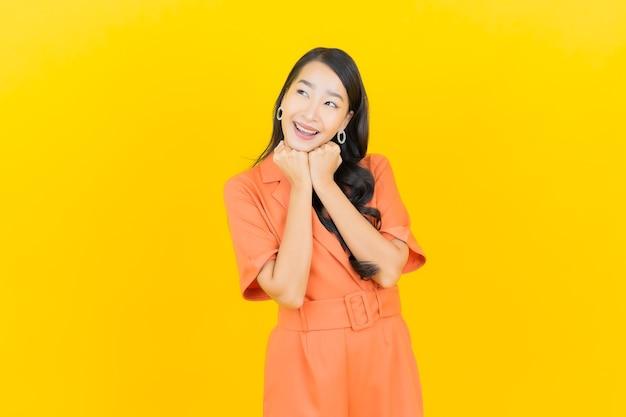 노란색에 행동과 초상화 아름 다운 젊은 아시아 여자 미소
