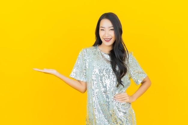 Улыбка женщины портрета красивая молодая азиатская с действием на желтом Бесплатные Фотографии