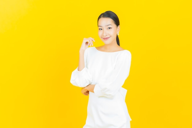 Улыбка женщины портрета красивая молодая азиатская с действием на желтом