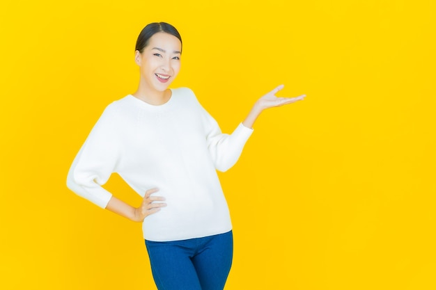 黄色のアクションで肖像画美しい若いアジアの女性の笑顔