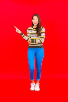 Portrait beautiful young asian woman smile with action on red isolated wall