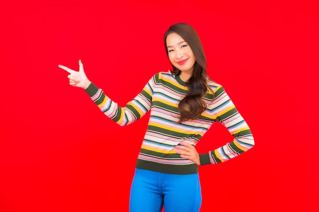 Sorriso di bella giovane donna asiatica del ritratto con azione sulla parete isolata rossa
