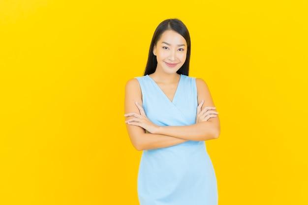 Sorriso di bella giovane donna asiatica del ritratto con azione sulla parete di colore giallo