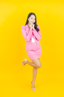 Portrait beautiful young asian woman smile with action on yellow color wall