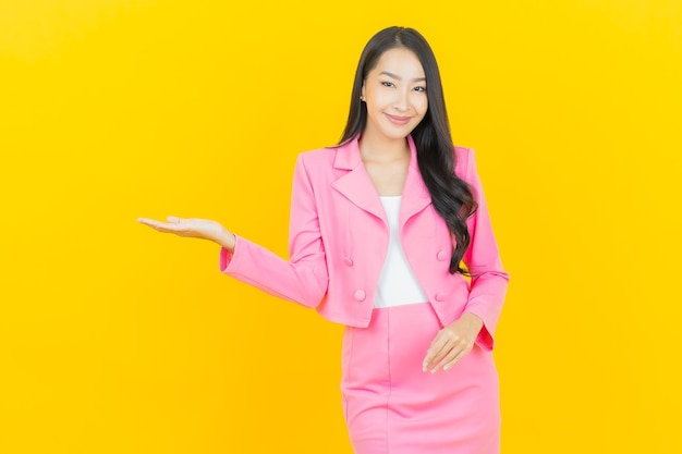 Portrait beautiful young asian woman smile with action on yellow color wall Free Photo