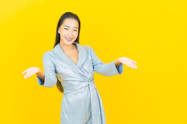 Portrait beautiful young asian woman smile with action on yellow wall