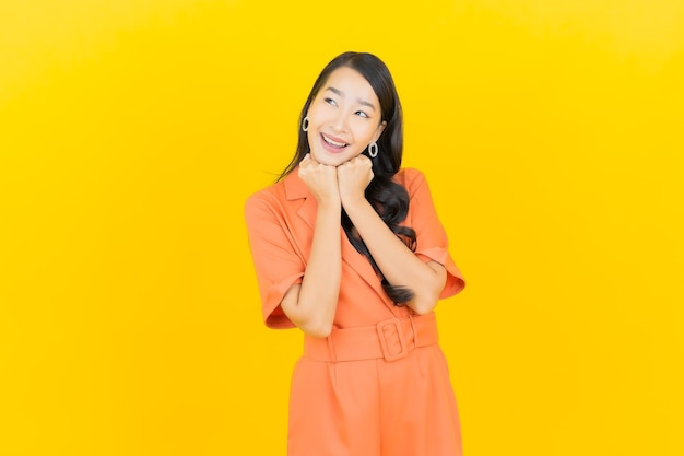 Sorriso della bella giovane donna asiatica del ritratto con azione sul giallo