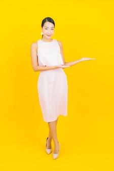 与行动的画象美丽的年轻亚裔妇女微笑在黄色