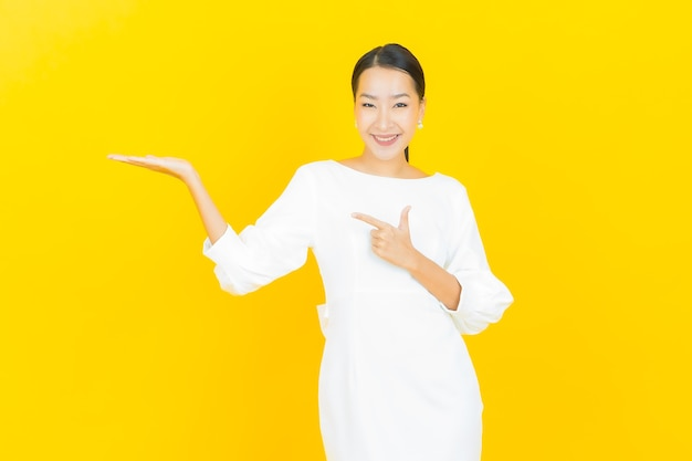 Ritratto bella giovane donna asiatica sorriso con azione su yellow