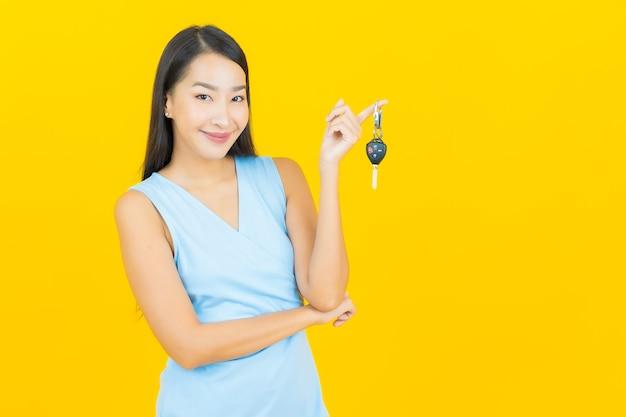노란색 벽에 자동차 키와 초상화 아름 다운 젊은 아시아 여자 미소
