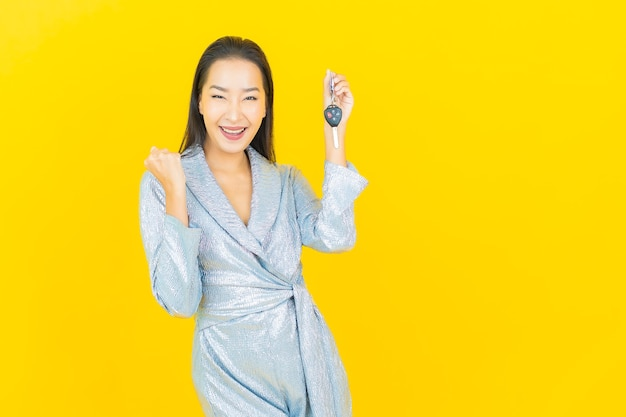 黄色の壁に車のキーと肖像画美しい若いアジアの女性
