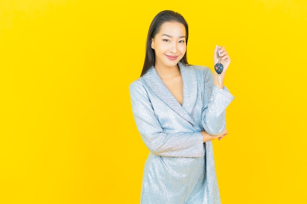 Portrait beautiful young asian woman smile with car key on yellow wall
