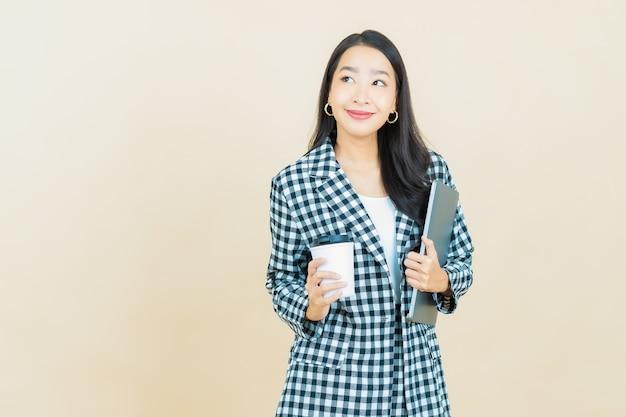 격리 된 배경에 컴퓨터 노트북과 초상화 아름 다운 젊은 아시아 여자 미소