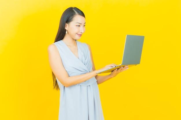 Улыбка женщины портрета красивая молодая азиатская с компьтер-книжкой компьютера на изолированной предпосылке