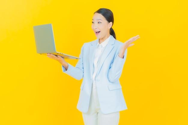 孤立した背景の上のコンピューターのラップトップと肖像画美しい若いアジアの女性の笑顔