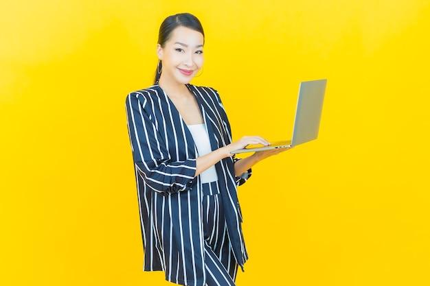 고립 된 배경에 컴퓨터 노트북과 초상화 아름 다운 젊은 아시아 여자 미소