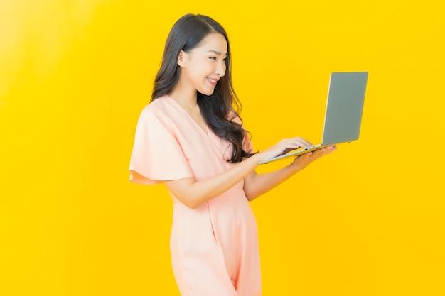 외진 벽에 컴퓨터 노트북을 들고 웃고 있는 아름다운 젊은 아시아 여성 초상화