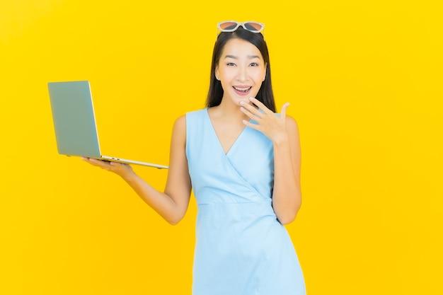Улыбка женщины портрета красивая молодая азиатская с компьтер-книжкой компьютера на желтой изолированной стене