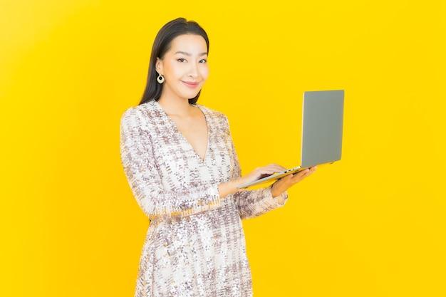 Улыбка женщины портрета красивая молодая азиатская с компьтер-книжкой компьютера на желтом