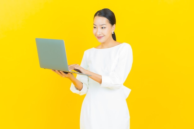 黄色のコンピューターのラップトップと肖像画美しい若いアジアの女性の笑顔