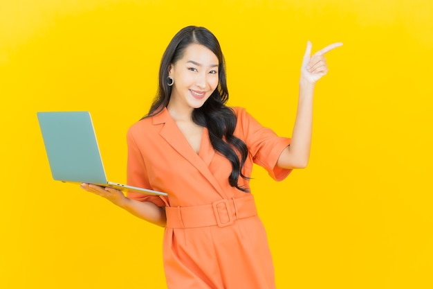 Portrait beautiful young asian woman smile with computer laptop on yellow