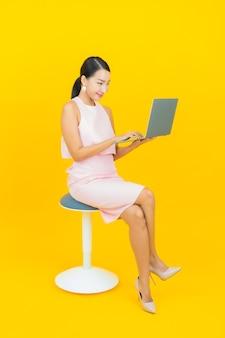 Ritratto bello giovane sorriso asiatico della donna con il computer portatile del computer su colore giallo
