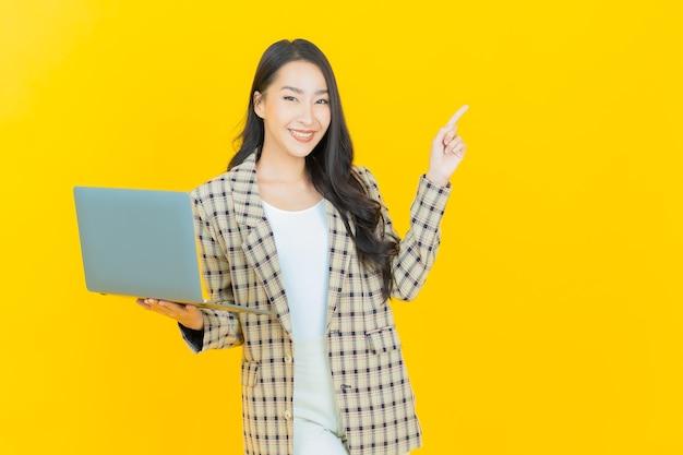 세로 컴퓨터 노트북으로 아름 다운 젊은 아시아 여자 미소